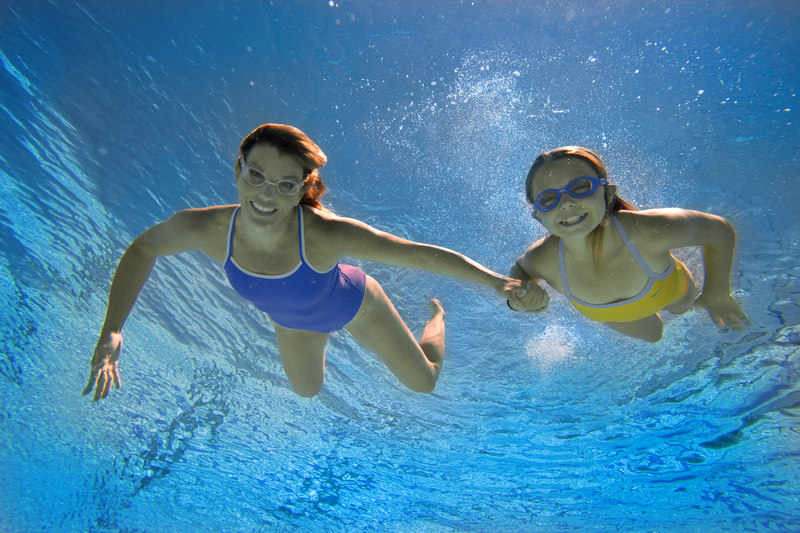 Mother and daughter swimming safely in pool water